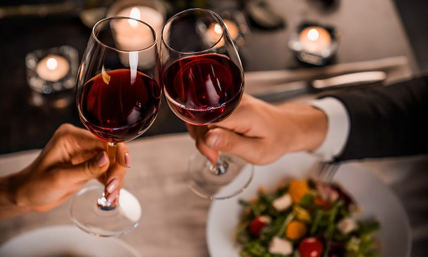 A man and a lady clinking two glasses of red wine over a candle lit restaurant meal