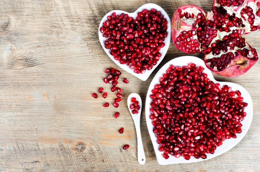two small white heart shaped bowls filled with pomegranate seeds
