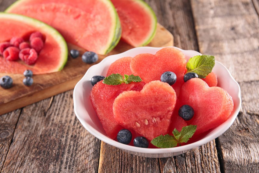 heart shaped watermelon slices in a small white bowl topped with blueberries and small mint leaves