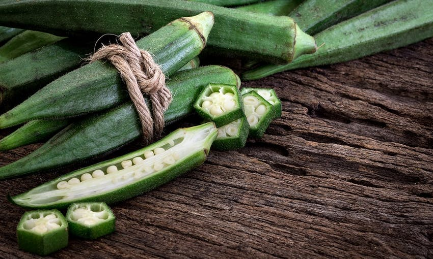 stalks of okra tied up with brown string and a stalk of okra cut in half