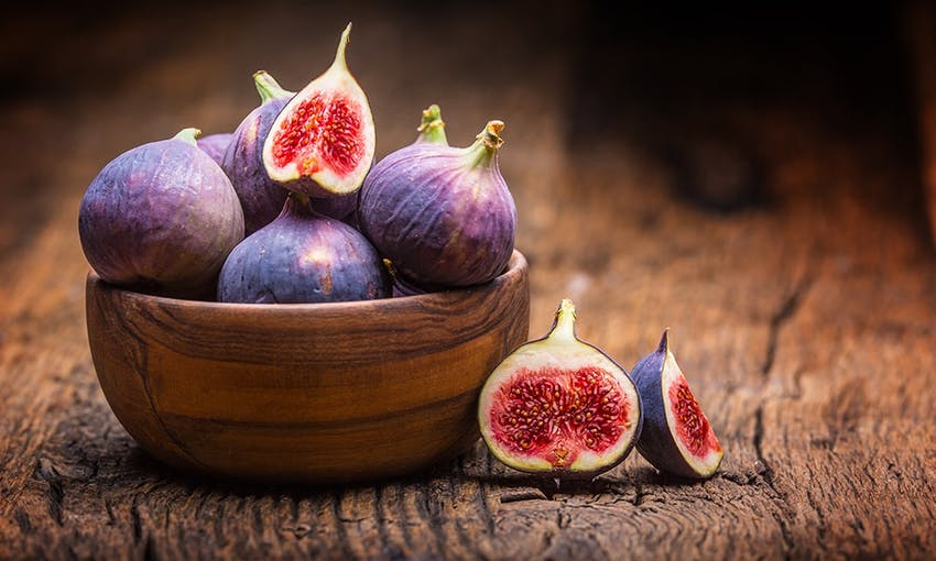 a wooden bowl with a pile of purple figs, some whole, some halved on top of a wooden table