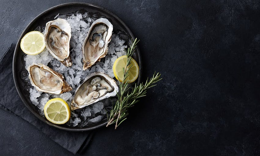 four oysters placed in a dark black bowl on top of shaven ice with two sprigs of rosemary and three wedges of lemon