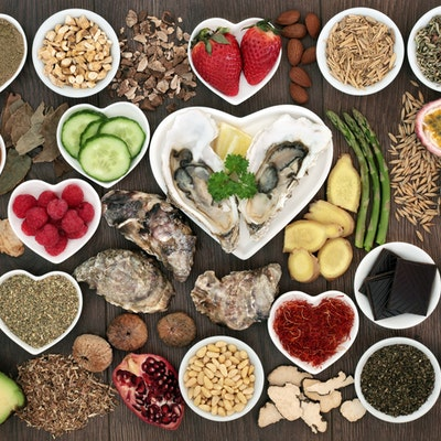 a birdseye view of different aphrodisiac foods, strawberries, asparagus, dark chocolate, cucumber, avocado and seeds in small circular and heart shaped dishes on a wooden table