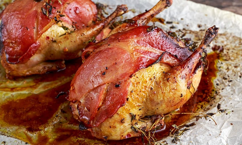two roasted partridges topped with herbs and streaky crispy bacon