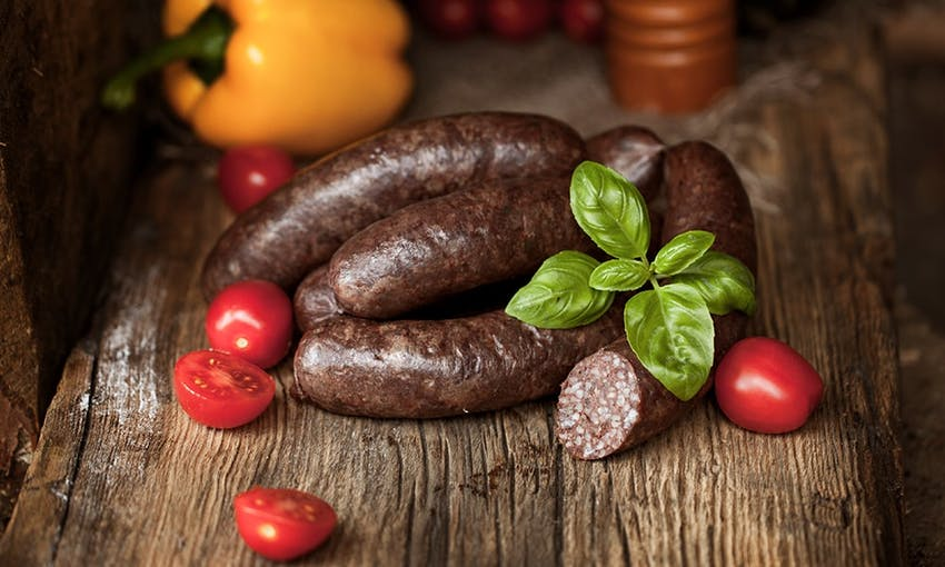 four black pudding sausages on an oak wooden chopping board with half diced cherry tomatoes and a yellow pepper in the background