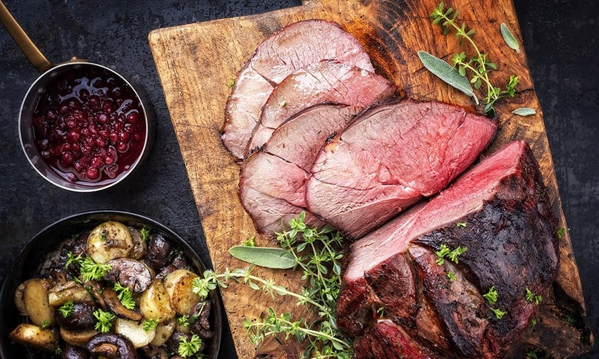 a roasted joint of venison on a wooden chopping board with a small saucepan of cranberry sauce and a side dish of roast potatoes and mushrooms