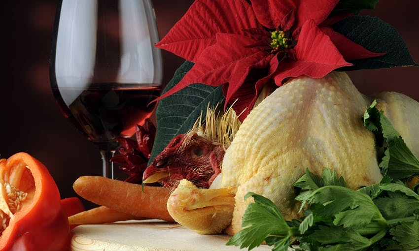 a capon on a white chopping board surrounded by fresh herbs peppers carrots and a christmas wreath red flower and a glass of red wine