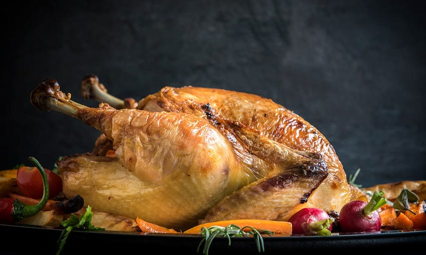 a whole roast turkey with crispy skin surrounded by roasted vegetables