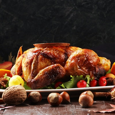 a table set for christmas dinner with a hot roasted turkey in the centre of a long wooden table  with pine cone decorations