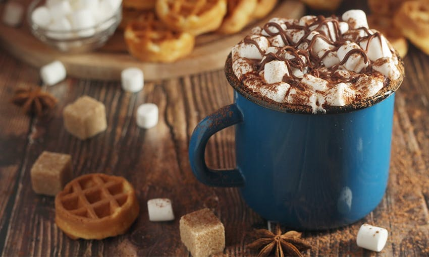 Blue mug of hot chocolate topped with marshmallows, caramel drizzle on a wooden table with mini waffles, sugar cubes and marshmallows