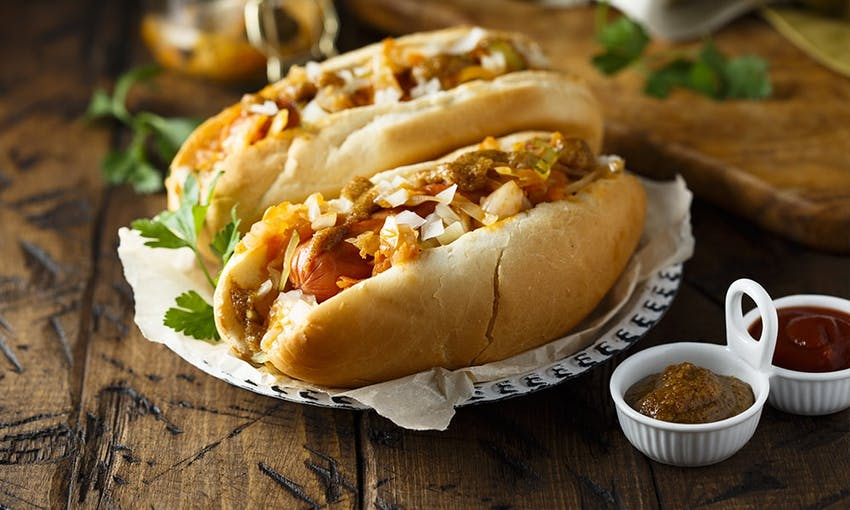 Hot dogs in crusty bread roll topped with a range of onions served with fresh herbs and dipping sauce