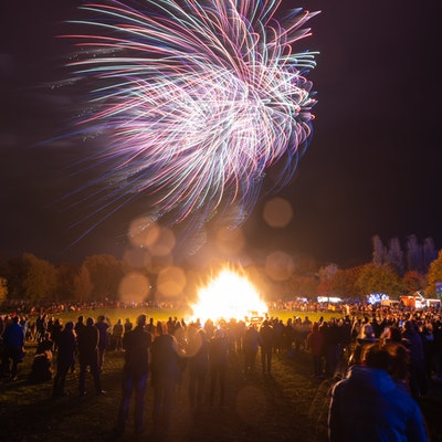 Crowds gather around large bonfire surrounded by autumnal trees with fireworks lighting up the sky