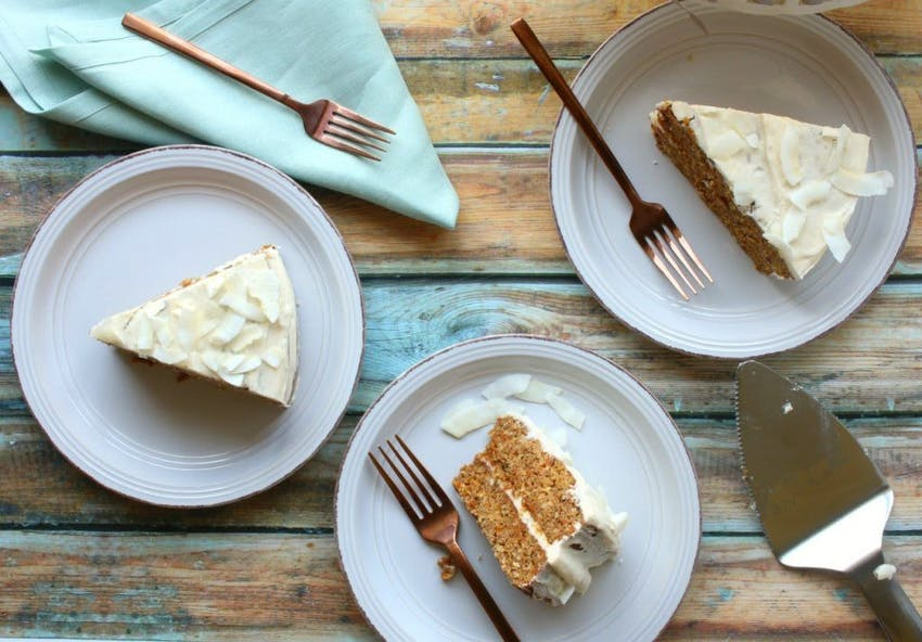 Three slices of carrot cake with frosting laid out on wooden table with light blue tablecloth and cutlery