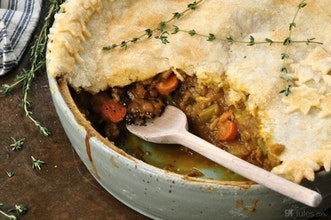 half open pie with hearty warming meat filling in a ramekin topped with a sprig of herbs