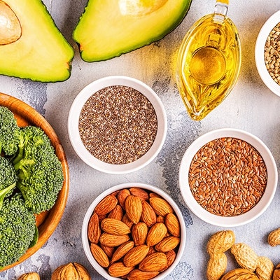 healthy dishes consisting of avocado, broccoli, seeds, nuts and vegetables on a wooden table