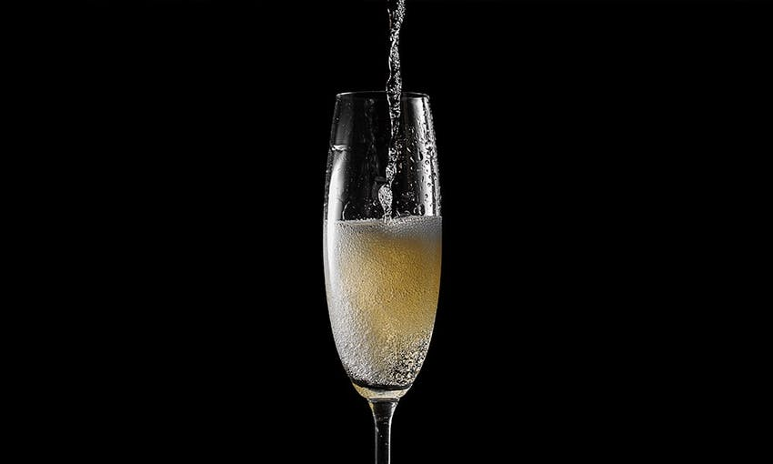 Prosecco glass in the centre of a black background with wine being poured from above