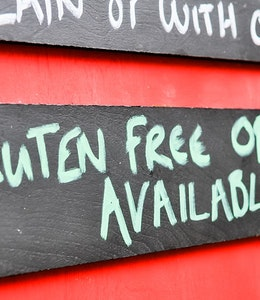 Menu board with  wooden gluten free options available sign