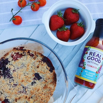 Berry cobbler in clear baking dish next to a bottle of real good ketchup and bowl of strawberries