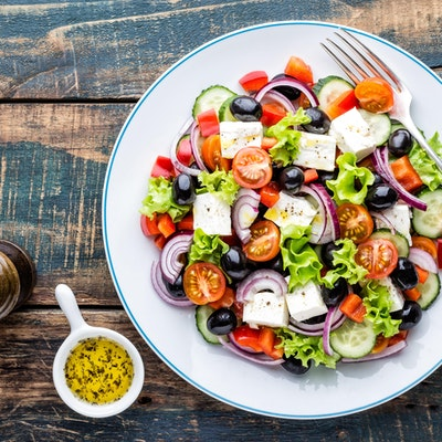 tasty greek salad of feta lettuce tomatoes red onion tomato cucumber and olives with a dressing and pepper grinder