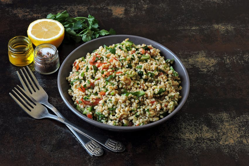 a bowl of chopped parsley, tomatoes, mint, onion, soaked bulgar, olive oil, lemon juice, salt and pepper