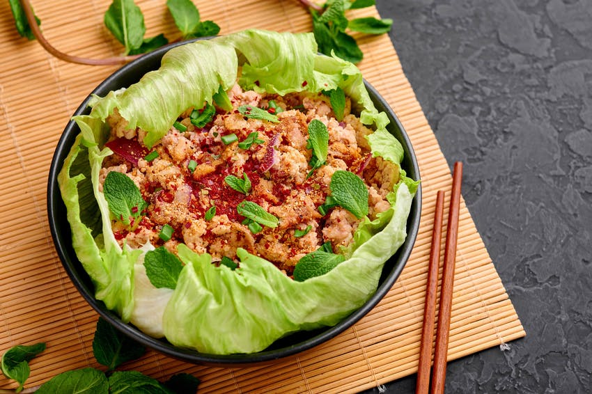a salad of lettuce, minced meat, chilli, lime, onion and herbs