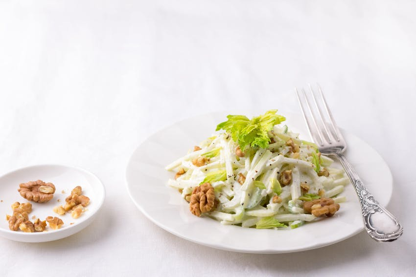 a salad consisting of celery apples walnuts grapes lettuce and mayonnaise