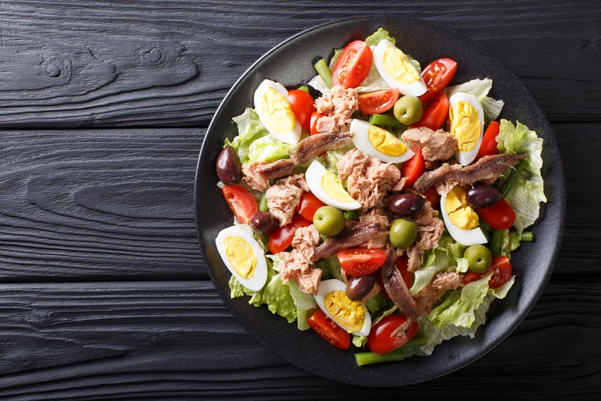 a plate of tomatoes hard boiled eggs nicoise olives anchovies cucumbers olive oil and tuna