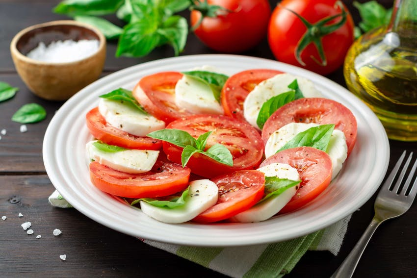 a plate of layered sliced mozerella and sliced tomatoes sweet basil olive oil and salt