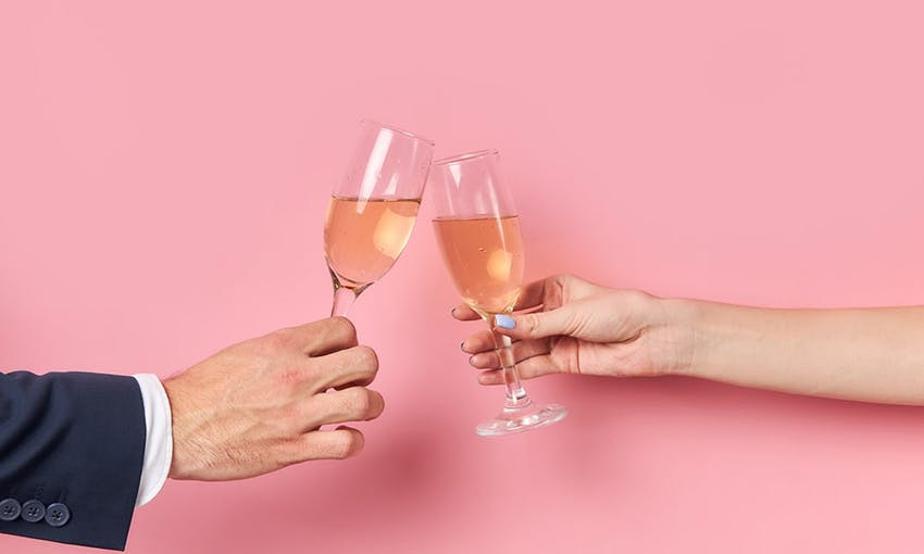the arms of a man in a suit and a lady clinking two prosecco glasses filled with sparkling tea in front of a pink background