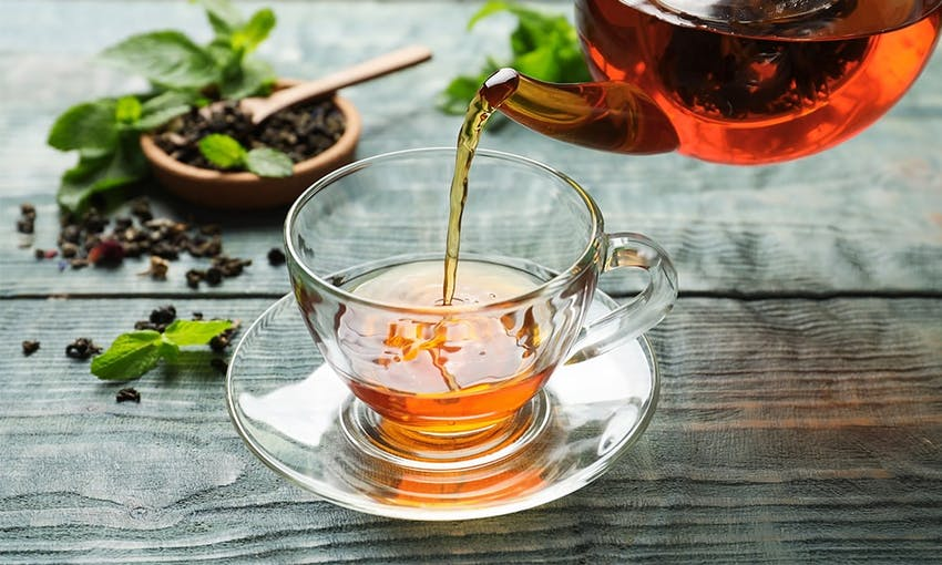 hot herbal tea in a clear glass cup and saucer with hot tea being poured in from a teapot next to a small dish of tea leaves