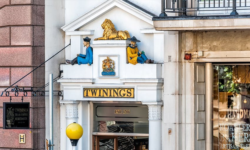 white twinings store front with golden lion and english lions shield with two figurines sat above entrance