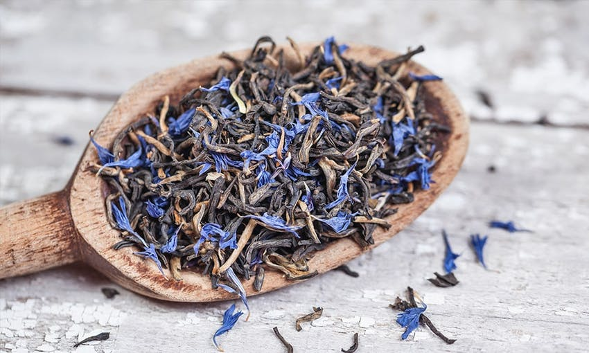 Wooden spoon full of earl grey tea leaves