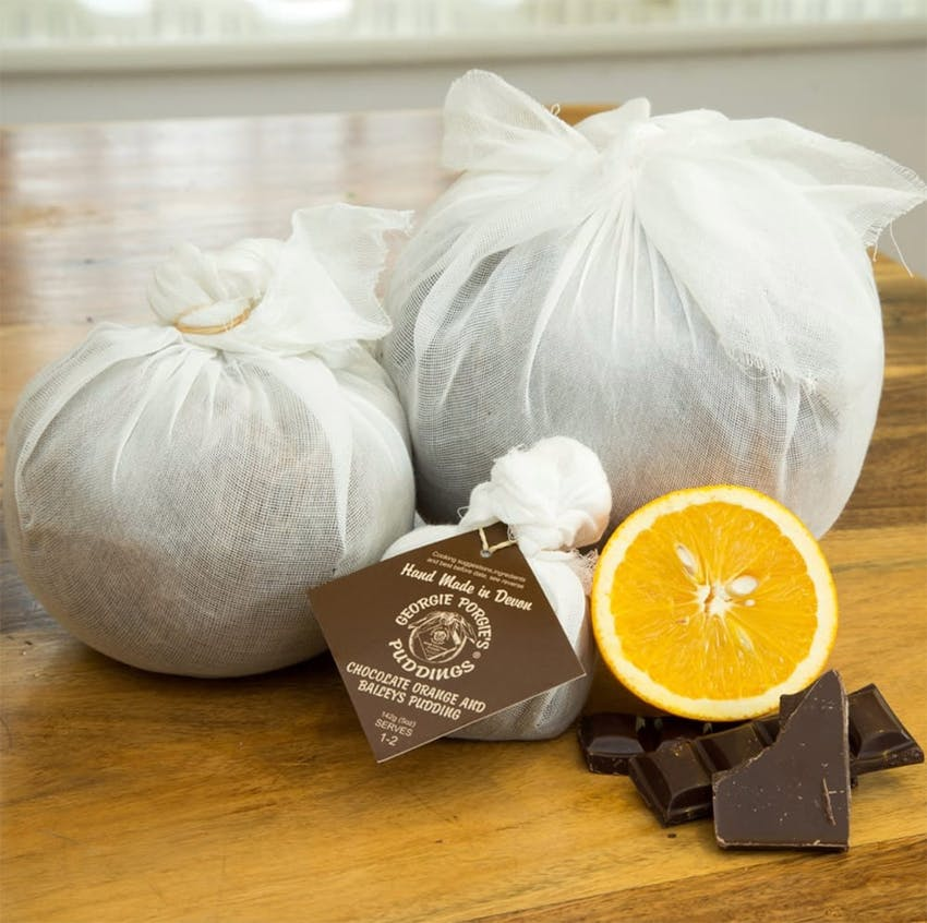 Georgie Porgie Puddings wrapped up and packaged on wooden table with dark chocolate and oranges