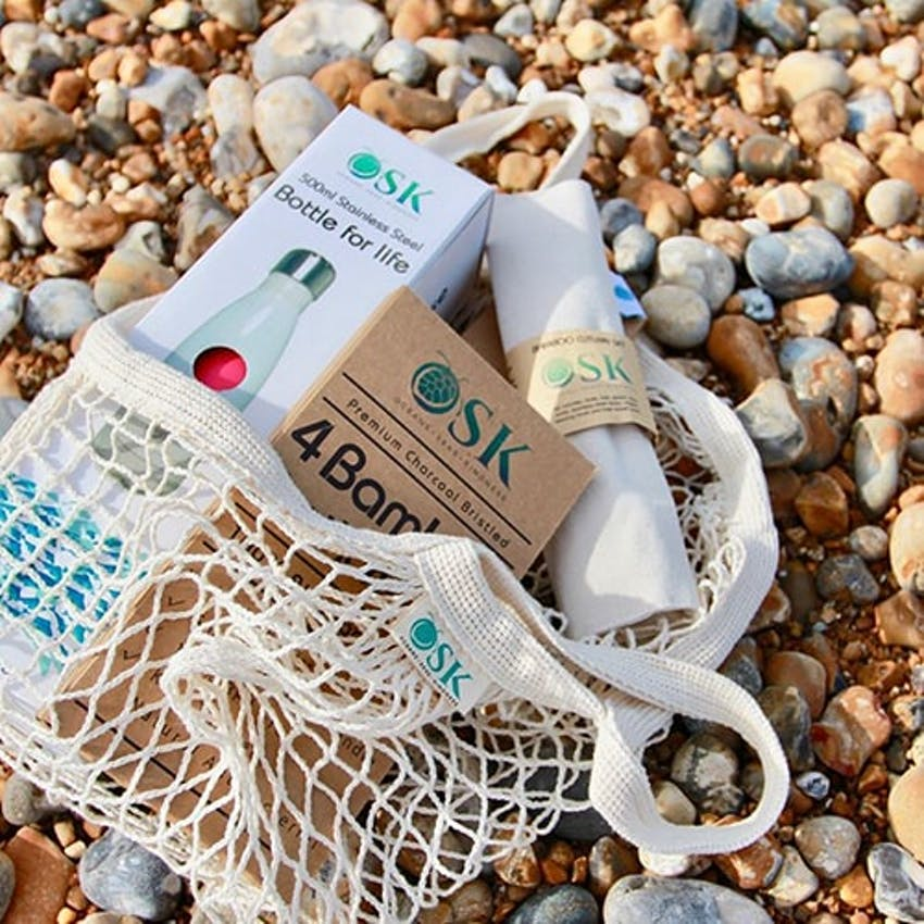 OSK Eco sustainable net bag with other eco friendly OSK products layed across a stony shingle on the beach