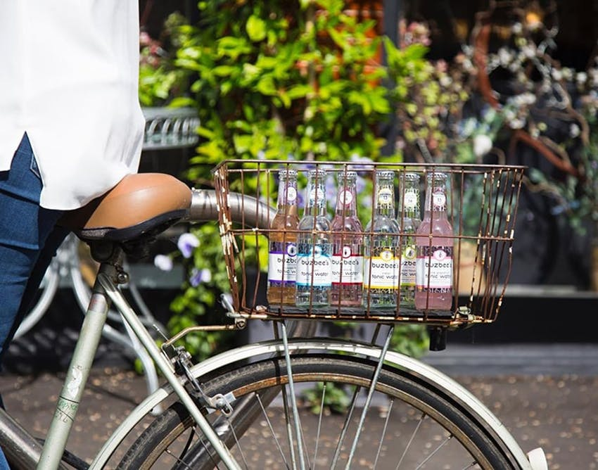 Man riding vintage bicycle outdoors with a range of buzbees tonics in the basket
