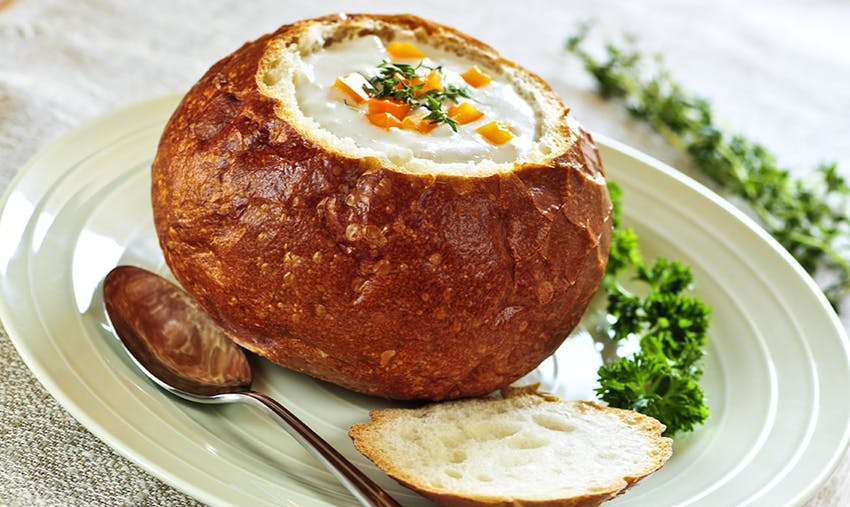 crusty sourdough bread with top cut off and filled with soup served with kale on a white plate and silver soup spoon
