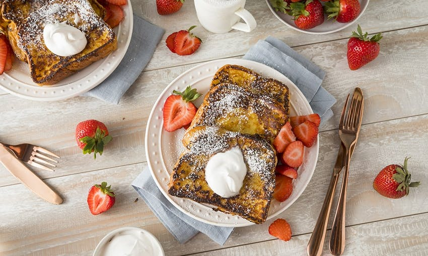 a breakfast spread of french brioche toast topped with icing sugar, cream and fresh strawberries