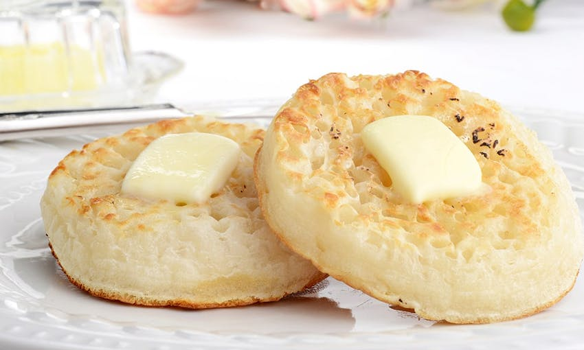 two crumpets with a knob of butter melting in the middle served on a white plate