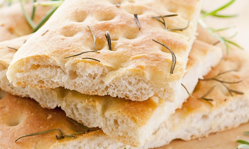 a stack of focaccia topped with herbs