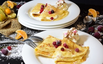 two plates of sweet crepes on a decorated table dusted with icing sugar and topped with berries