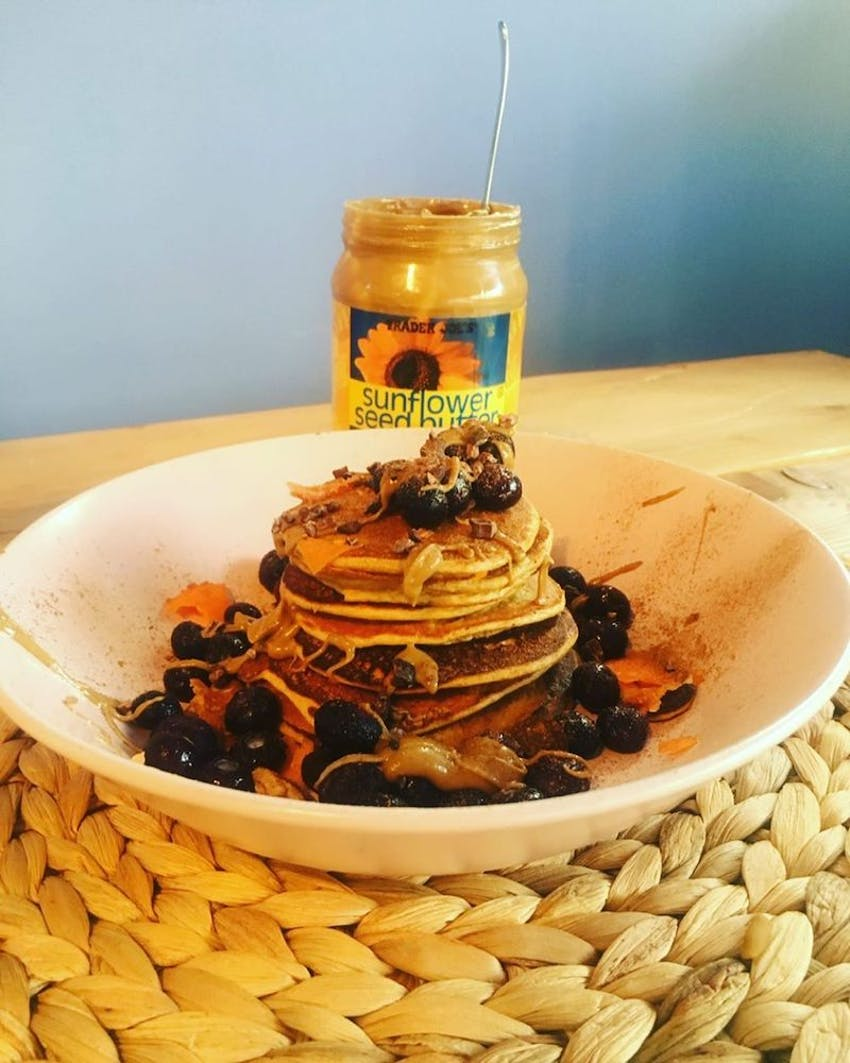a stack of pancakes topped with sunflower seed butter and frozen berries
