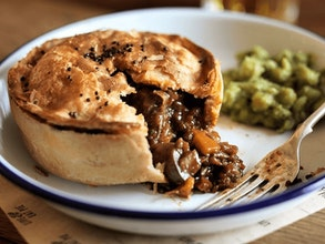 a crusty pie with a vegan mushroom tomato and red wine onion and thyme filling served with mushy peas