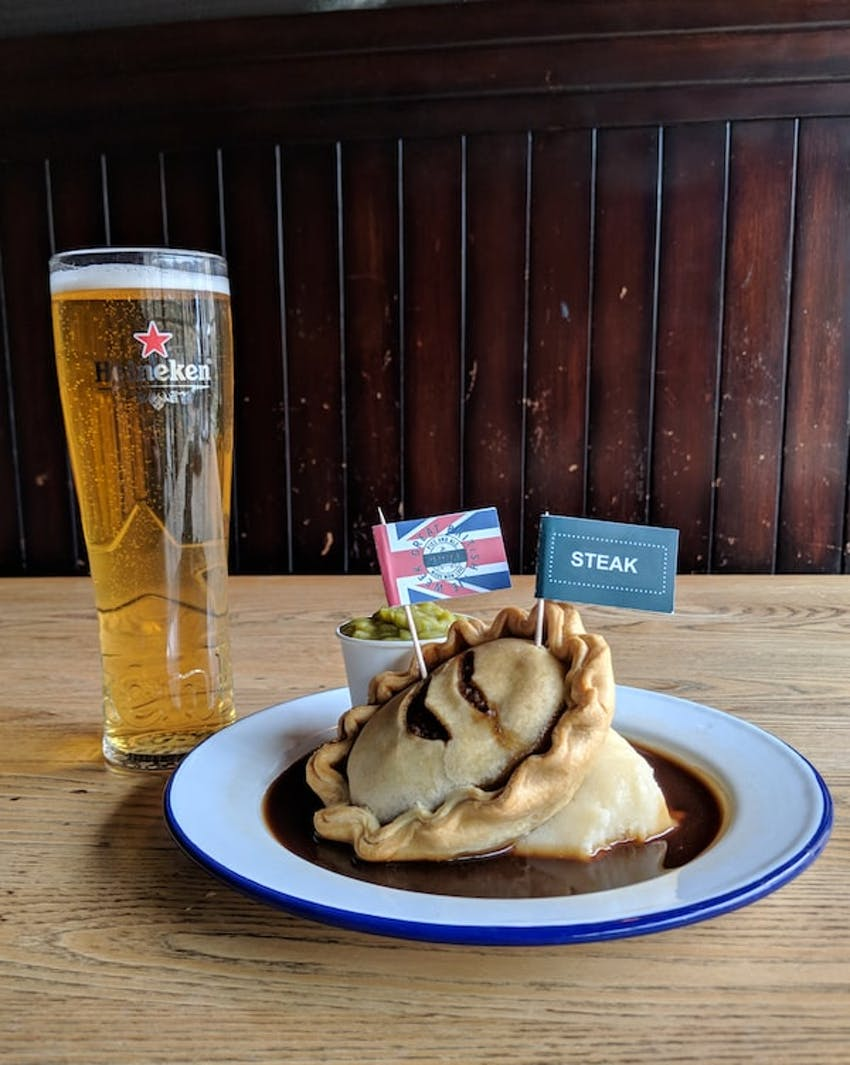 redhouse steak pie swimming in gravy with a side of peas and a heineken beer