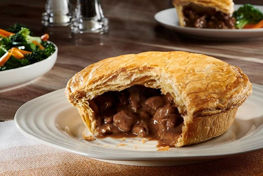 a large sliced open steak and ale pukka pie with meat and filling oozing out