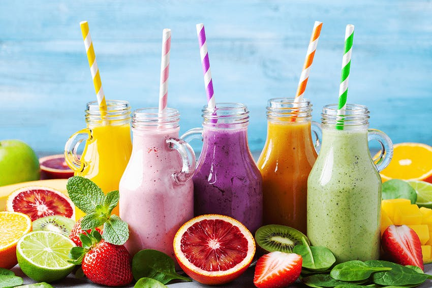 yellow, pink, purple, orange and green smoothies in glass jars with striped spoons surrounded by fresh fruit