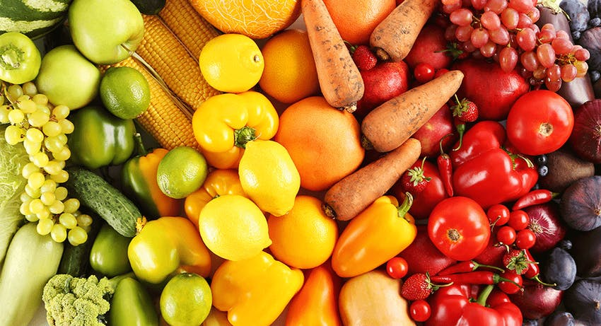 colourful spectrum of fruits and vegetables going from green through to yellow through to orange to red and then purple