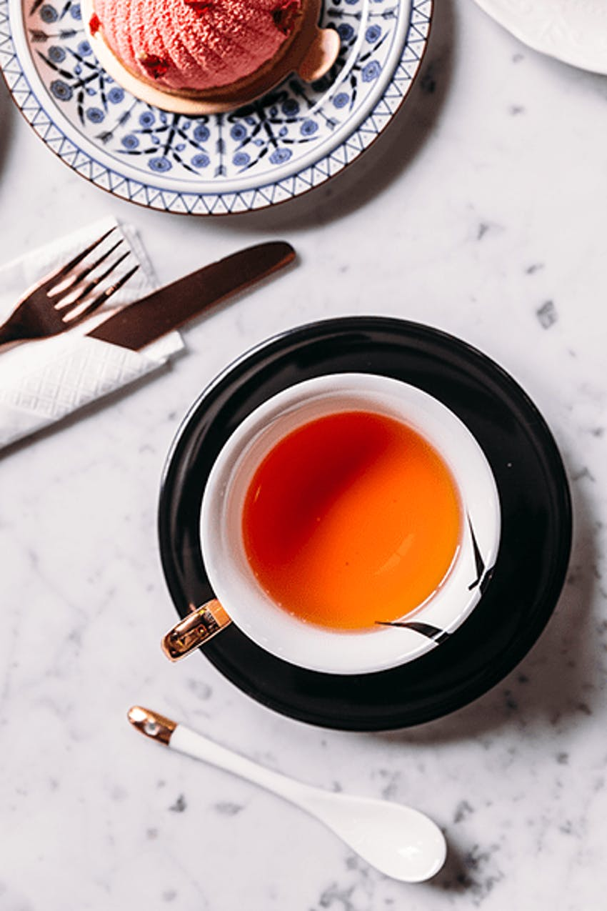 Mug of herbal tea in saucer
