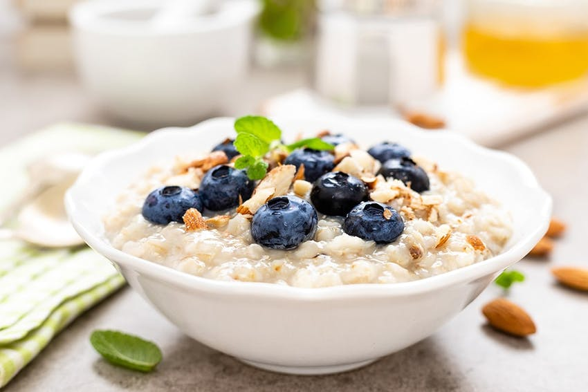 a bowl of creamy porridge topped with fresh blueberries almonds and sprigs of mint
