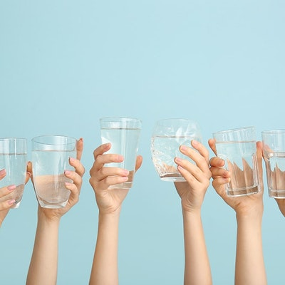 six hands holding up clear glasses of water