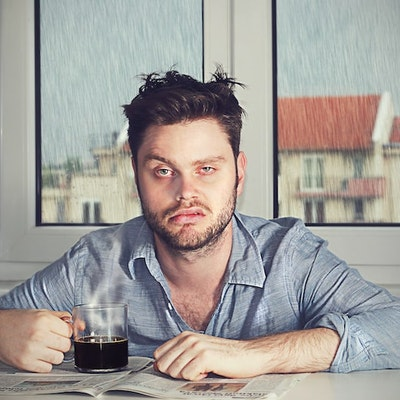 a tired hungover man with a defeated expression sat infront of a window where it is raining outside with a black coffee